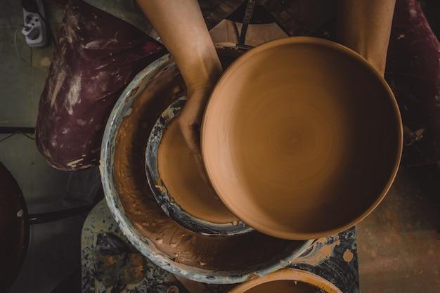 Meester potter houdt een ronde kleiplaat in zijn handen onder de pottenbakkersschijf. beeldhouwer beeldhouwt pottenproducten van witte klei. atelier aardewerk. meester kruik. creativiteit. culturele tradities. handgemaakt. ambacht