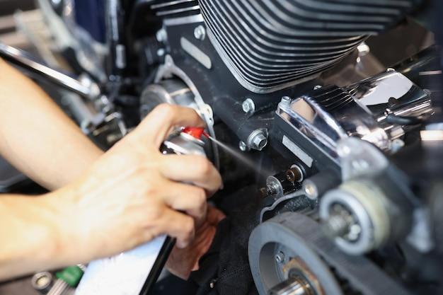 Meester reparateur puffend vet op motorfiets onderdeel close-up reparatie en onderhoud van