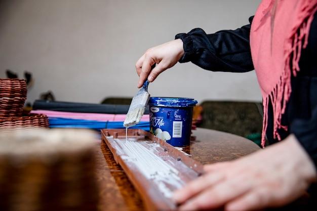 Meester schilderen van een stuk hout in het atelier. hoge kwaliteit foto