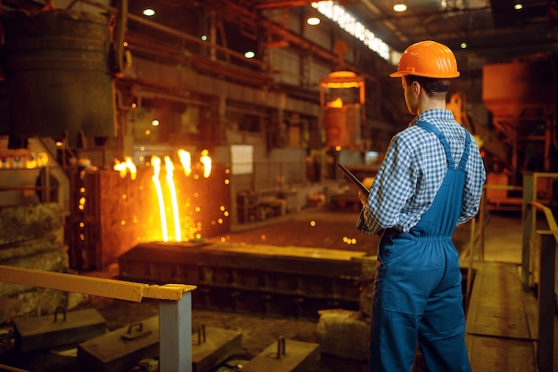 Meester staalmaker in helm bij oven met vloeibaar metaal, staalfabriek, metallurgische of metaalverwerkende industrie, industriële productie van ijzerproductie op molen