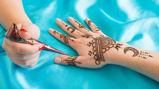 Meester tatoeëren prachtige mehndi aan de hand van de vrouw