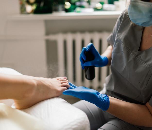 Meester tijdens een pedicure. het proces van professionele pedicures. het concept van schoonheid en gezondheid.