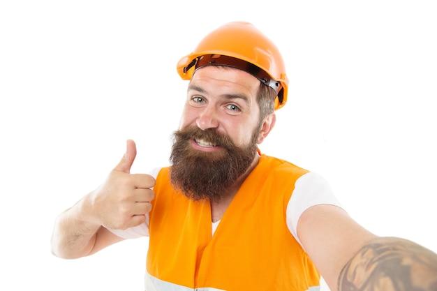 Meester toegewijd aan superieure kwaliteit en resultaten. meesterbouwer geeft duimen op. bebaarde man meester gelukkig lachend geïsoleerd op wit. werknemer in beschermende helm en veiligheidsvest. meester van het ambacht.