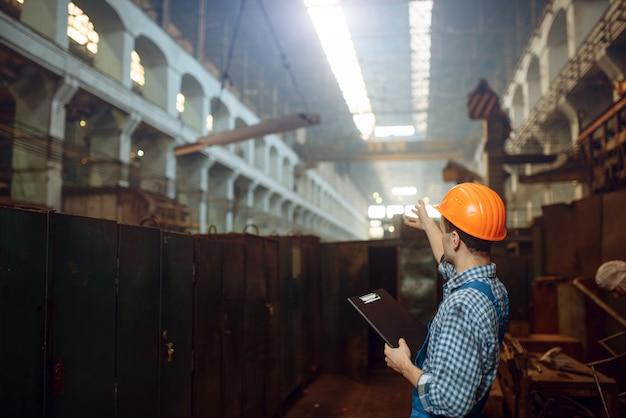 Meester toont duimen naar kraanmachinist, fabriek