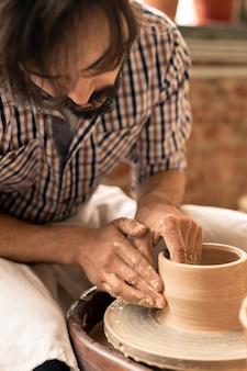 Meester van aardewerk dat over een draaiend wiel buigt terwijl hij de vorm van een pot vormt tijdens het werken over nieuw aardewerk