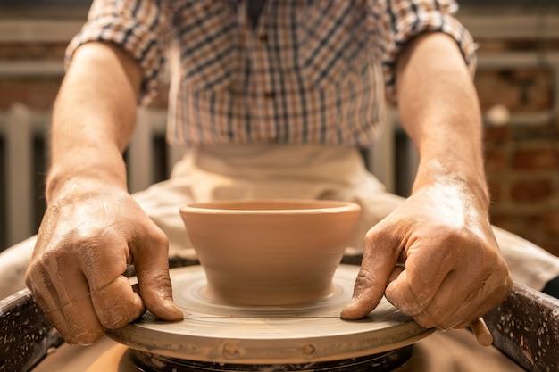 Meester van aardewerk die speciaal draad uitrekt voor het snijden van klei-item van het roterende wiel tijdens het werken over een nieuwe kom
