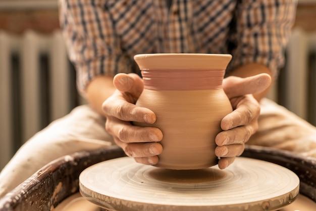 Meester van aardewerk of jonge ambachtsman die nieuwe aarden pot boven wiel houdt terwijl hij aan nieuwe collectie aardewerk werkt