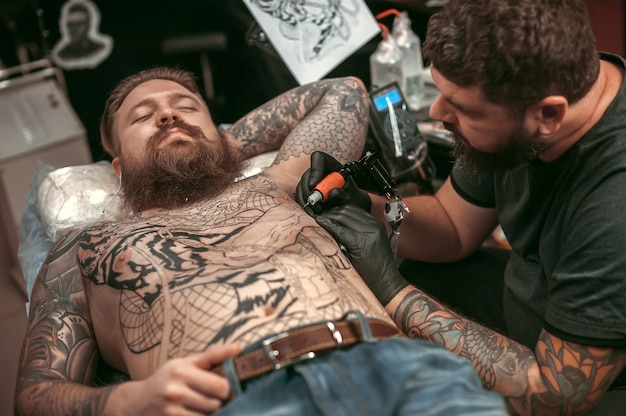 Meester van de kunst van het tatoeëren bezig met professioneel tattoo machinegeweer in salon.
