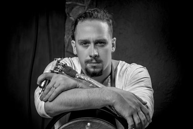 Meester van de kunst van het tatoeëren en een tattoo-pistool in de studio