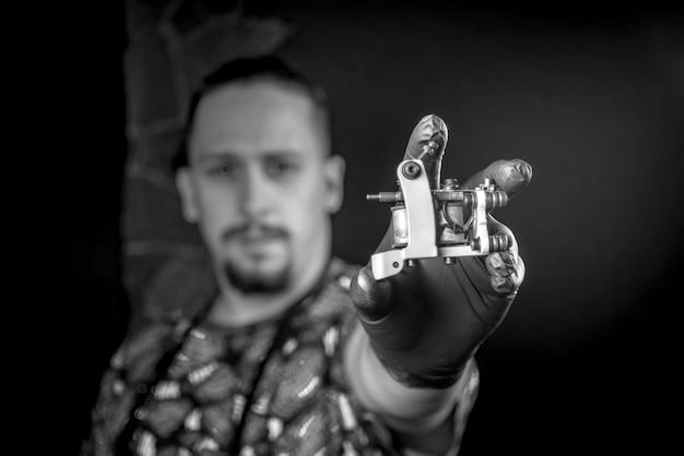 Meester van de kunst van het tatoeëren en een tattoo-pistool in tattoo-studio.