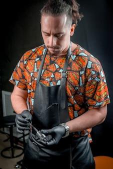 Meester van de kunst van het tatoeëren in een tattooshop.