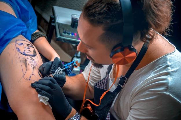 Meester van de kunst van het tatoeëren maakt een tatoeage op de klant in de tattoo-studio