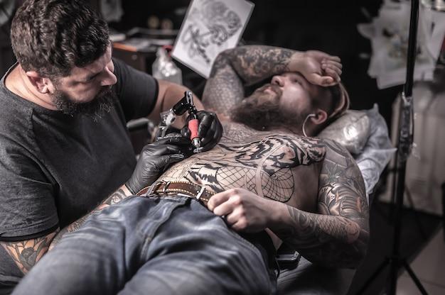 Meester van de kunst van het tatoeëren poseren in een tattoo salon