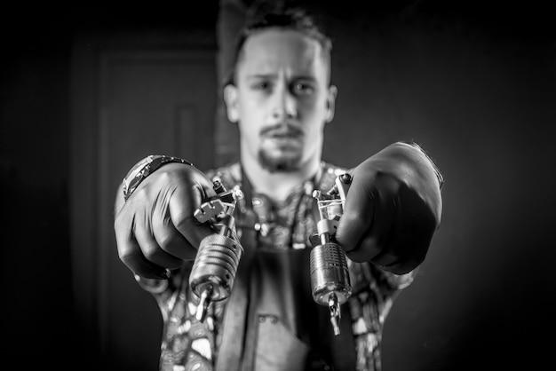 Meester van de kunst van het tatoeëren poseren in tattoo studio