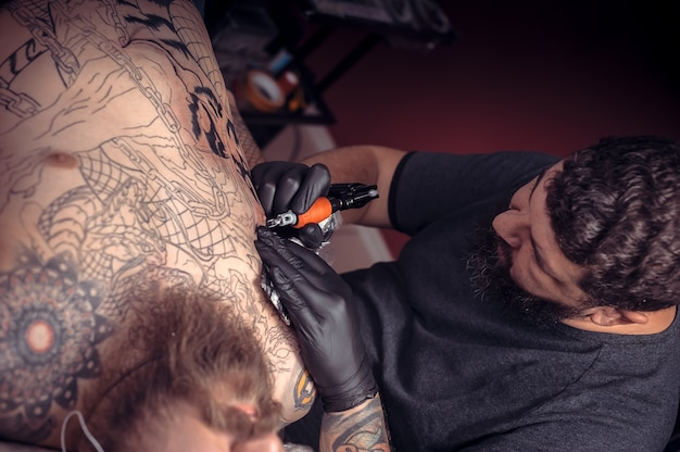 Meester van de kunst van het tatoeëren werkt in een tattoo-salon