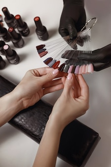 Meester van manicure in zwarte handschoenen, ophalen met het palet van de klant, voorbereiding voor het aanbrengen van gel polish. spa faciliteiten. manicure kamer.