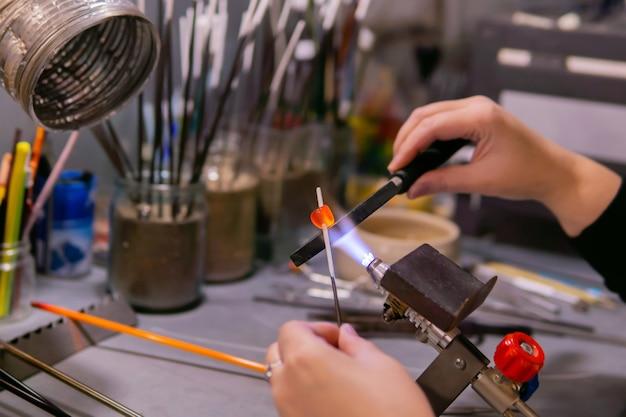 Meesterhanden vormen een glaskraal tijdens het maken van kralen in een glasblazerij