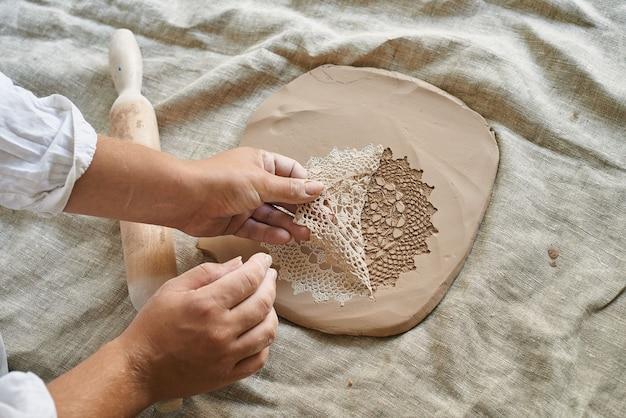 Meestervakman rolt de klei op de tafel, brengt het servetpatroon over op de kleimassa