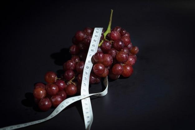 Meet rond de taille en rode druiven op een zwarte achtergrond.