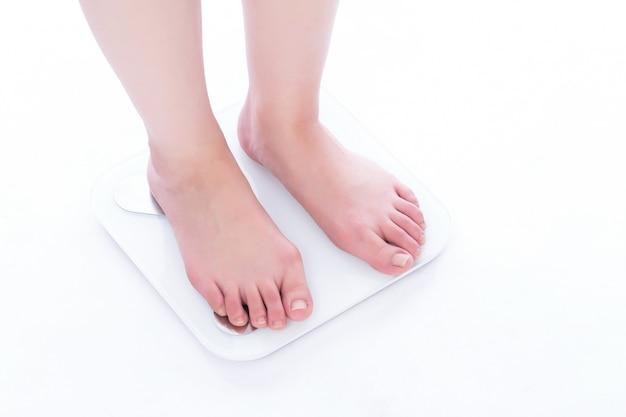 Meet schaal om uw gewicht te controleren met een witte achtergrond.