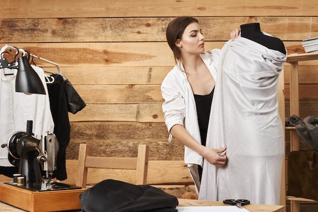 Meet twee keer en snijd één keer. portret van gerichte jonge kaukasische ontwerper van kledingstuk planning van nieuwe concept van kleding op etalagepop, met behulp van liniaal en stof, willen naaien nieuwe jurk op naaimachine