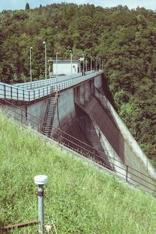 Meetinstrumenten (rekstrook en topografisch niveau) voor stabiliteitsbewaking op een dam.