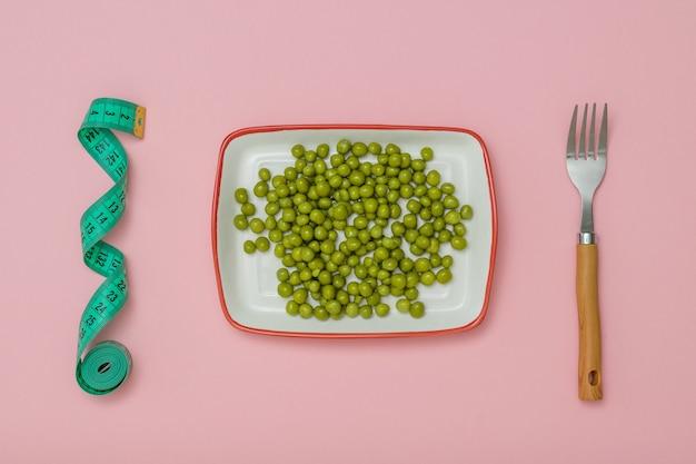 Meetlint, een kopje ingeblikte erwten en een vork op een roze achtergrond. het concept van een gezond dieet voor gewichtsverlies.