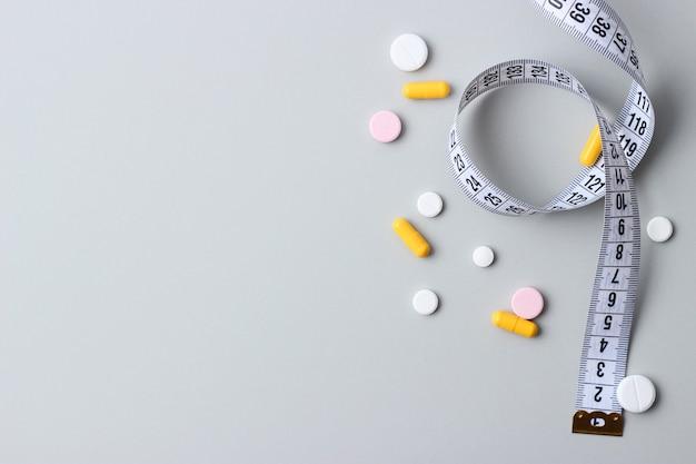 Meetlint en dieetpillen op een gekleurde close-up als achtergrond. dieetplan, voedingssupplementen, hulp bij vetverlies, gewichtsbeheersing. hoge kwaliteit foto