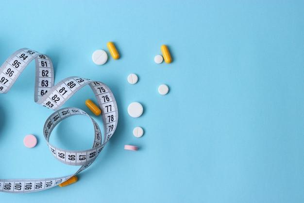 Meetlint en dieetpillen op een gekleurde close-up als achtergrond