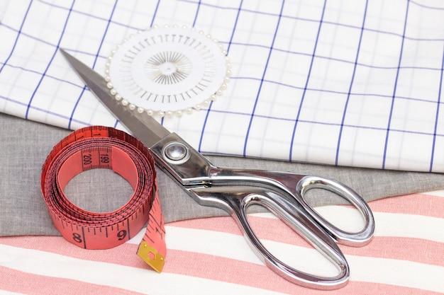 Meetlint en schaar is op een katoenen stof. naaiconcept, naaien van natuurlijke stoffen.