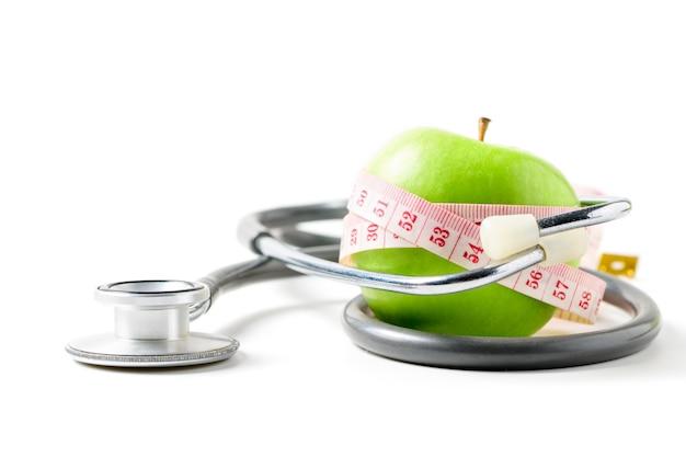 Meetlint gewikkeld rond een groene appel met geïsoleerde stethoscoop, concept van het doel om af te vallen, het doel van een dieet