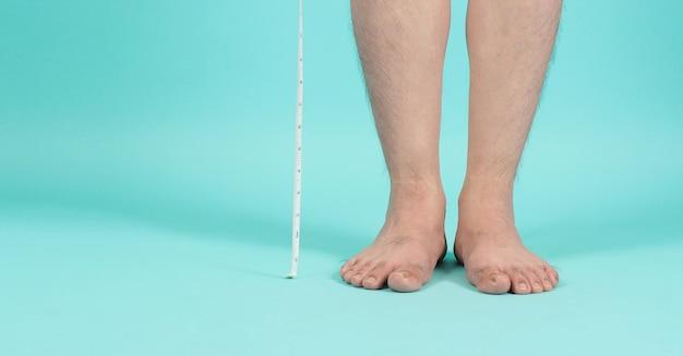 Meetlint in handen met blote voeten en benen op mintgroene kleur of tiffany blue achtergrond.