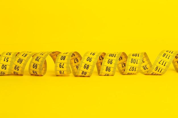 Meetlint op een gele achtergrond. meetlint in de vorm van een spiraal op een gele achtergrond. afslanken en dieet concept, kopie ruimte