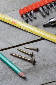 Meetlint, schroeven en schroevendraaier liggen op een houten ondergrond. detailopname.