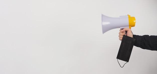 Megafoon en zwart gezichtsmasker in mannenhand en hij draagt een zwart shirt op een witte achtergrond. studio-opnamen.