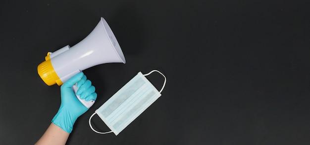 Megafoon in de hand en het dragen van blauwe latex handschoen en gezichtsmasker op zwarte achtergrond. studio-opnamen.