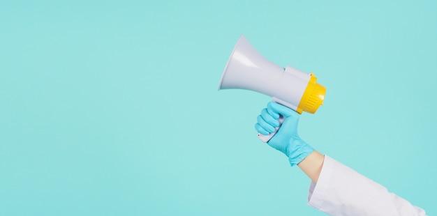 Megafoon in de hand. man draagt doktersjurk en blauwe medische handschoen op mintgroen of tiffany blue achtergrond. studio-opnamen.