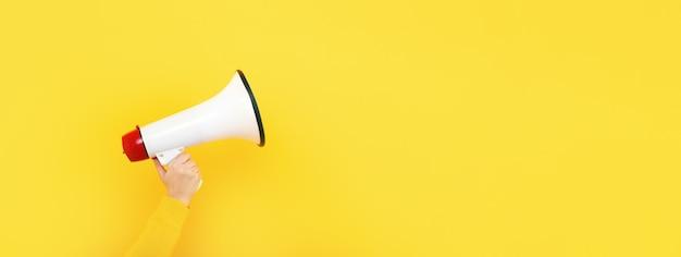 Megafoon in de hand op een gele achtergrond, aandacht concep