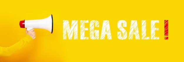 Megafoon in de hand op een gele muur, concept mega sale,