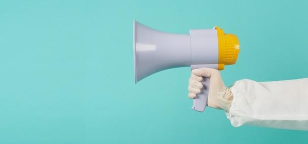 Megafoon in handen van de vrouw op groene of tiffany blue achtergrond. .vrouw draagt pbm-pak en witte medische handschoen of latexhandschoen.