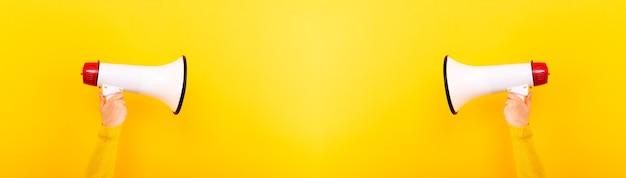 Megafoons in handen op een gele achtergrond, aandachtsconcept
