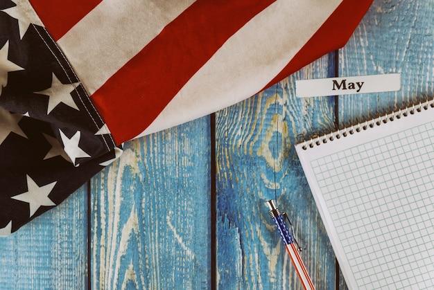 Mei-maand van kalenderjaar verenigde staten van amerika vlag van symbool van vrijheid en democratie met lege kladblok en pen op kantoor houten tafel
