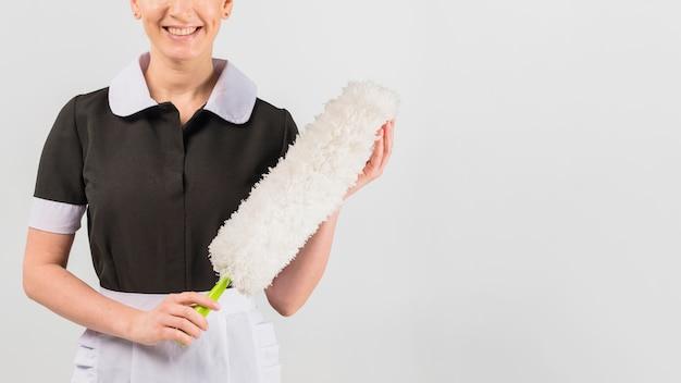Meid in uniform met stofdoek