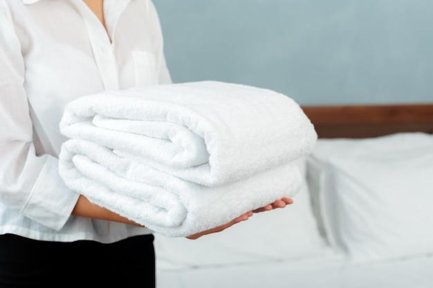 Meid met schone schone handdoeken tijdens het huishouden in een hotelkamer
