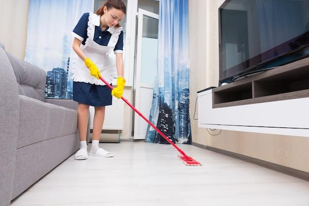 Meid of huishoudster in een nette witte schort die een woonkamervloer schoonmaakt met een kleurrijke rode dweil, lage hoekweergave op vloerniveau