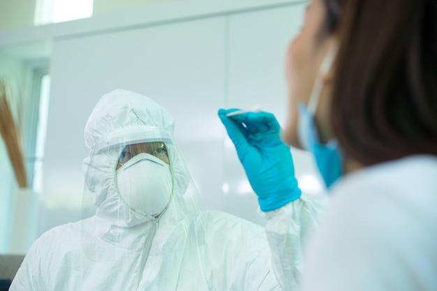 Meidcal gebruikt houten wattenstaafjes om een monster te houden om het coronavirus thuis te controleren en te onderzoeken.