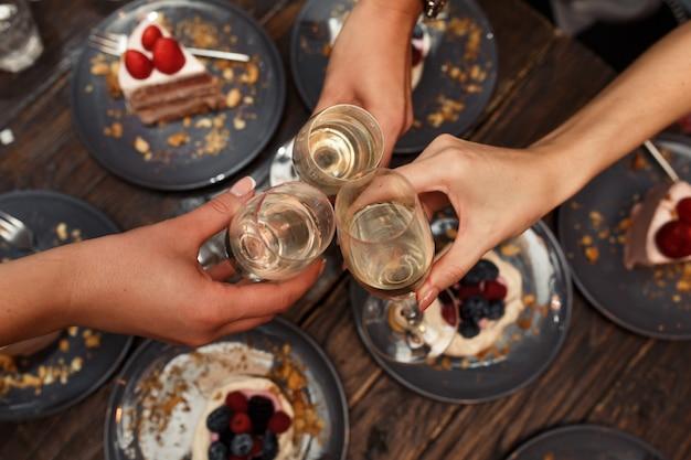 Meidenfeestje. de meisjes juicht glazen met champagne in restaurant toe.
