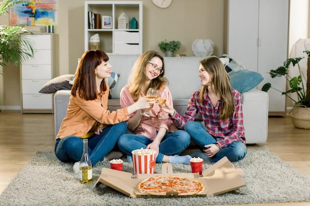 Meidenfeestje. feestelijke gelegenheid. dames in casual jeans en overhemden. gelukkige meisjes rammelende glazen met wijn, lachen, plezier maken. pizzaparty thuis van drie vriendinnen