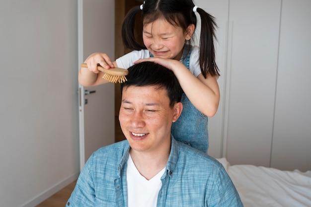 Meidum schoot kind dat vaders haar borstelt