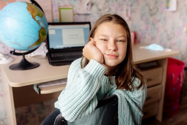Meisje 10 jaar oud in een masker op afstandsonderwijs thuis. het kind verveelt zich, hij is moe